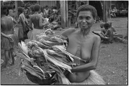 Mortuary ceremony: woman carries banana leaf bundles (wealth items) in basket