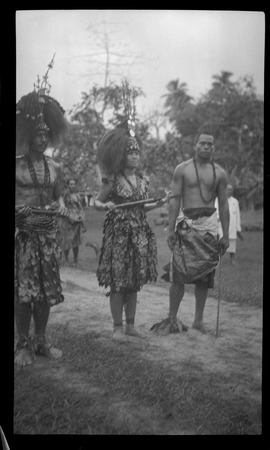 Three individuals with traditional Samoan clothing.