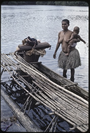 Canoes: woman holds infant, near a canoe used for coastal transport with basket and other items on board