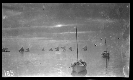 Boats at sea, canoes with sails.