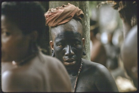 Mortuary ceremony: mourning woman with black paint on face and body, shaved head, wears turtle shell earrings and red shel...