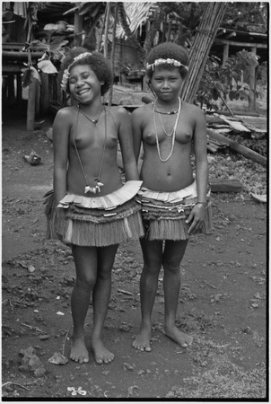Friendship: adolescent girls in short fiber skirts, necklaces and garlands, girl (l) wears mourning necklace