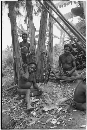 House-building for Rappaports: men smoke, taking a break from sharpening support posts with machetes