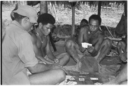 Men playing cards; in middle is Winitaemu.