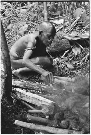 Boori'au and another woman cook taro.