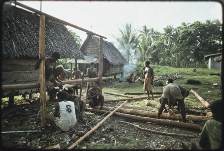 House-building: men take a break from building the frame for a new house