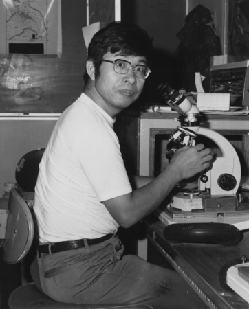 Chemist Toshio Ishizuka using a microscope in the core laboratory aboard the D/V Glomar Challenger (ship) during the Deep ...