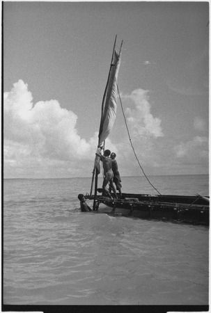 Canoes: men raise sail on an outrigger canoe