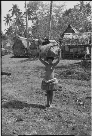 Young woman in short fiber skirt holds large basket on her head, village houses in background