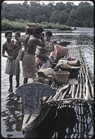 Canoes: man places basket of yams and other items onto canoe for coastal transport, women holding infants stand nearby