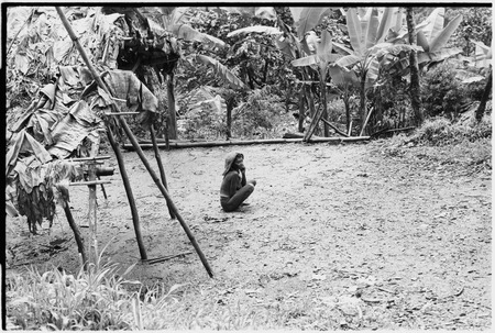 Woman with barkcloth cap sits in a garden clearing, Kumingo