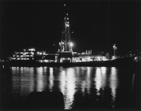 Night photograph of the D/V Glomar Challenger (ship) in Manzanillo, Mexico in a fuel dock. The bright light on the lower s...