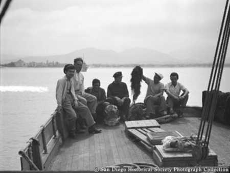 Group of men sitting on [American Agar Company?] boat, one holding up kelp