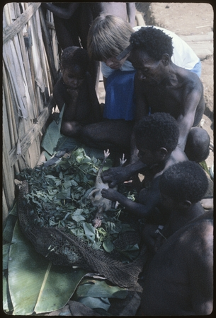 Food preparation: watched by children, Amangware and Komber, Ann Rappaport and Mer prepare chicken for cooking