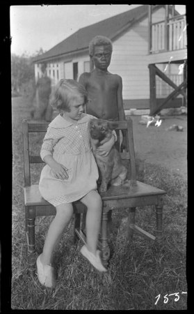 European girl on chair with dog, and Papua New Guinea boy behind.