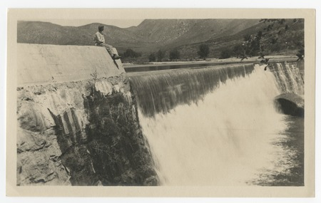 Young man seated above spillway at Boulder Creek diverting dam