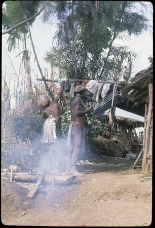 Akis (left) hangs up clothing and fabrics which he has purchased on a trip to Madang