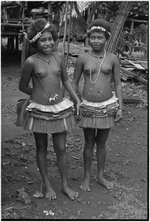 Friendship: adolescent girls wearing short fiber skirts, garlands and necklaces, girl (l) wears mourning necklace