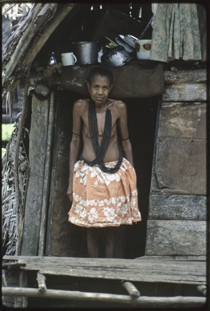 Momwarka's mother, wearing black mourning necklace, stands in doorway of small house, kitchen items above her