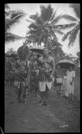 Group of people, two men in front wearing traditional samoan clothing.