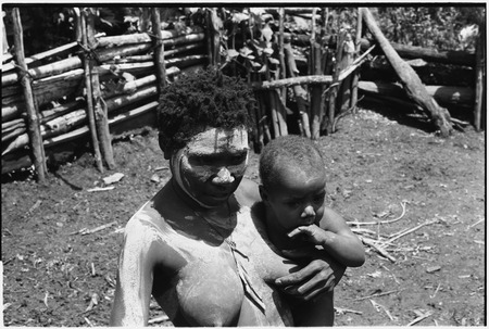 Bomagai: woman with face and body smeared with clay as a sign of mourning, she holds infant