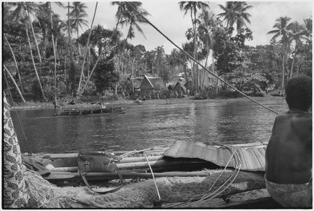 Tukwaukwa village on Kiriwina: seen from canoes in lagoon