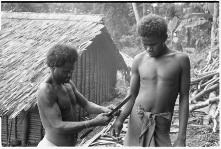 Man ties red cane obi on another man's wrist prior to a feast they are going to give.