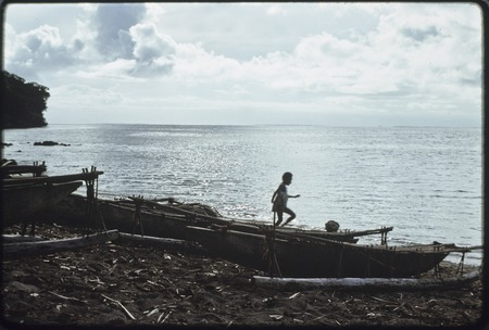 Child plays on beached canoes