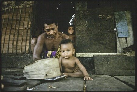 Man and baby on veranda, another child in house