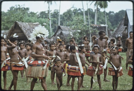 Dance: Motabasi (left) with feathers in hair, dancers wear fiber skirts and carry flattened pandanus leaves for circle dance
