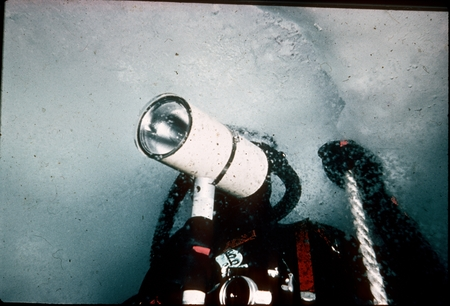 Scuba diver under ice and surrounded by ice crystals in Antarctica