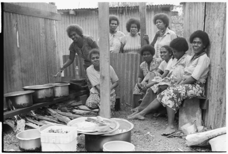 Christian women in a kitchen with walls of iron roofing.