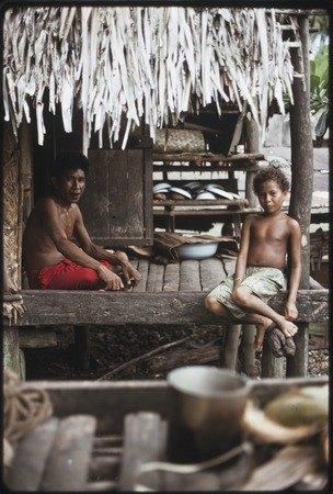 Man and boy sit on house veranda, kitchen equipment on shelves in background