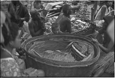Mortuary ceremony, Omarakana: large basket of exchange valuables, banana leaf bundles stacked, woman (l) smokes