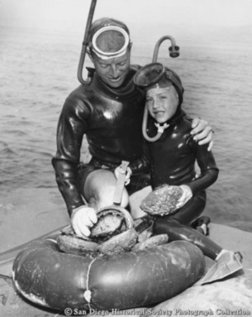 Father and son in diving suits posing with catch of abalone