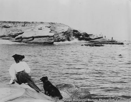 Woman and dog sitting on rock at La Jolla Cove