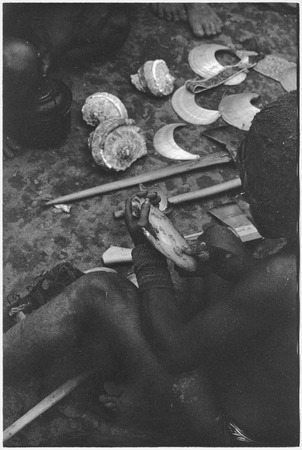 Ritual exchange, Tsembaga: man examines shell valuable, steel axes and other shells in background