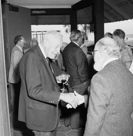 Roger Revelle shaking hands with William H. Thomas. Roger Revelle's 80th birthday party, March 7, 1989