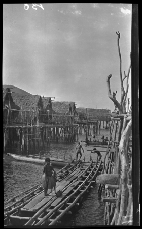 People in canoes, and houses on stilts over water at Gaile, also spelled Gaire, a Motu village in Central Province.