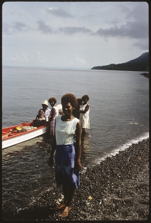 Portrait of woman. Solomon Islanders in back with canoe