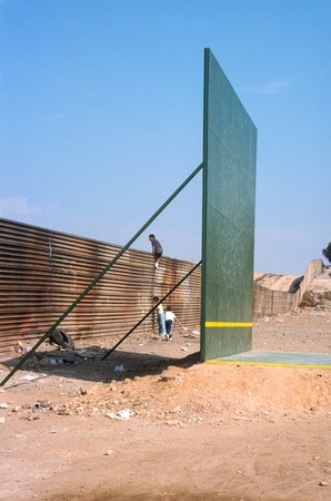 The Rules of the Game: ball court and border fence with children playing