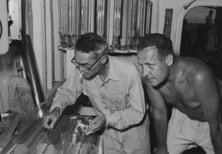 Milton Nunn Bramlette (left) and Roger Revelle are reviewing some core samples aboard the research vessel Spencer F. Baird...
