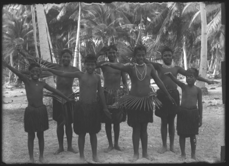 Boys posing in grass skirts, with waist and head piece.