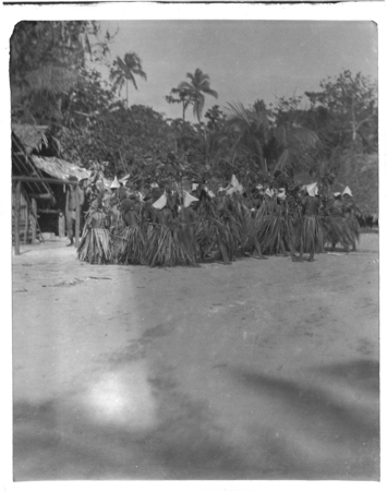 Santa Catalina dancers with leaf skirts and conical hats.
