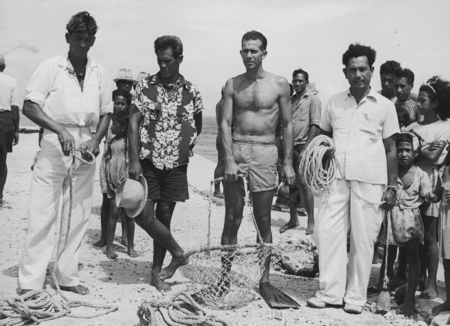(Left to right) Takaroan pearl divers Fereti and Tehaiere with diving goggles around their necks confer with Capricorn Exp...