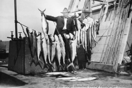 Two men posing with catch of yellowtail tuna