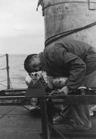 Robert Floyd Dill shown here is adjusting an underwater camera during the Capricorn Expedition (1952-1953) on board the re...