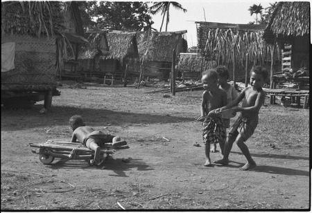 Children playing, pulling boy on a makeshift cart in Tukwaukwa village, Kiriwina