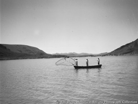 Fishermen casting net from small boat off coast of Baja California