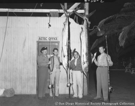 Clark Gable and three other men with fishing rods posing with swordfish caught from sportfishing boat Aztec